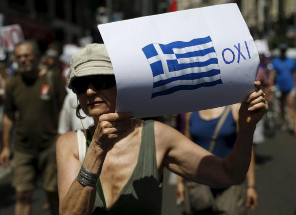 """A woman holds a placard with a Greek national flag next to a message in Greek reading, """"No"""" during a rally in support of Greece, in Madrid July 5, 2015.   REUTERS/Javier Barbancho."""